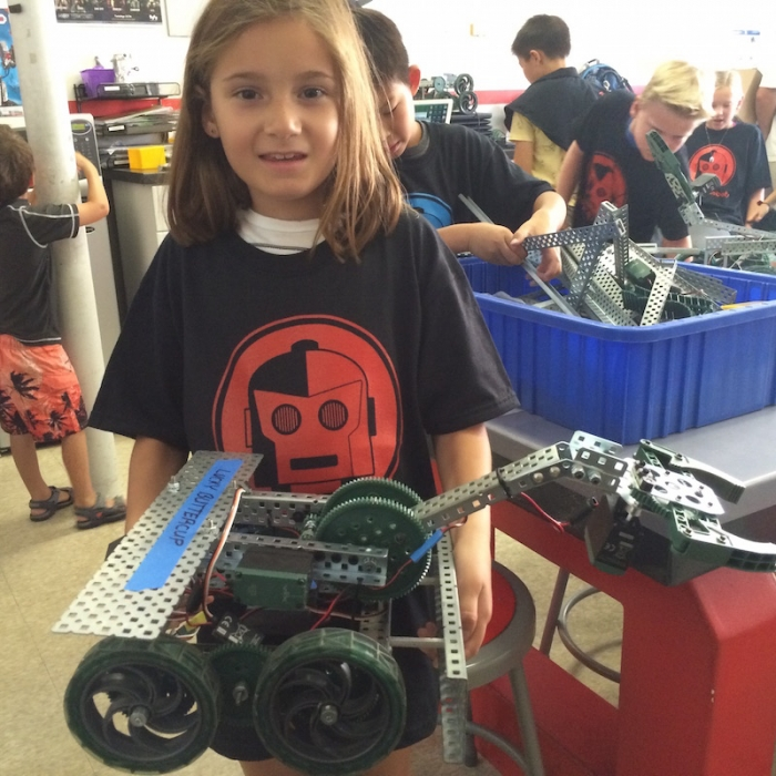 Young girl at Rolling Robots showing off her robot
